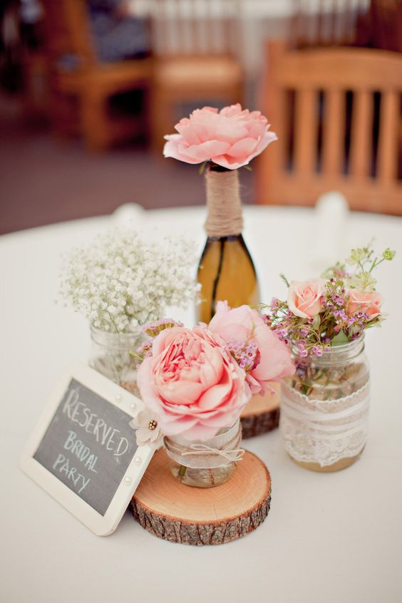 a rustic wedding centerpiece of wood slices, jars with lace, pink roses and baby's breath plus a chalkboard sign