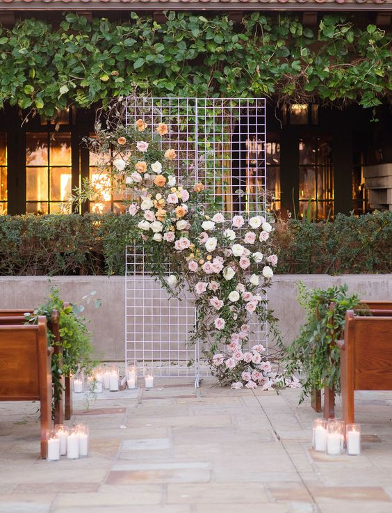 a simple modern wedding backdrop of mesh, white, pink and peachy blooms and foliage, candles on the ground is refined