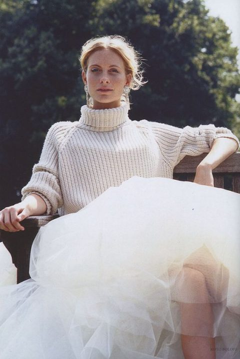 a slouchy chunky off white turtleneck sweater over a princess style wedding gown and statement earrings
