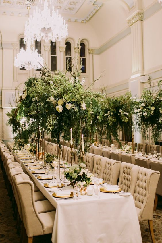 a sophisticated wedding reception space with lush and dimensional greenery and white bloom arrangements and centerpieces