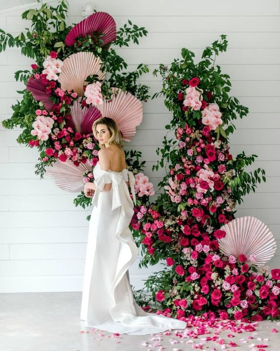 a super bold and lush wedding backdrop of greenery, pink, blush, fuchsia blooms and colorful fronds is just jaw-dropping
