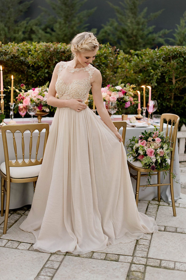 a tan wedding dress with a fully embellished bodice with no sleeves and a pleated maxi skirt with a train