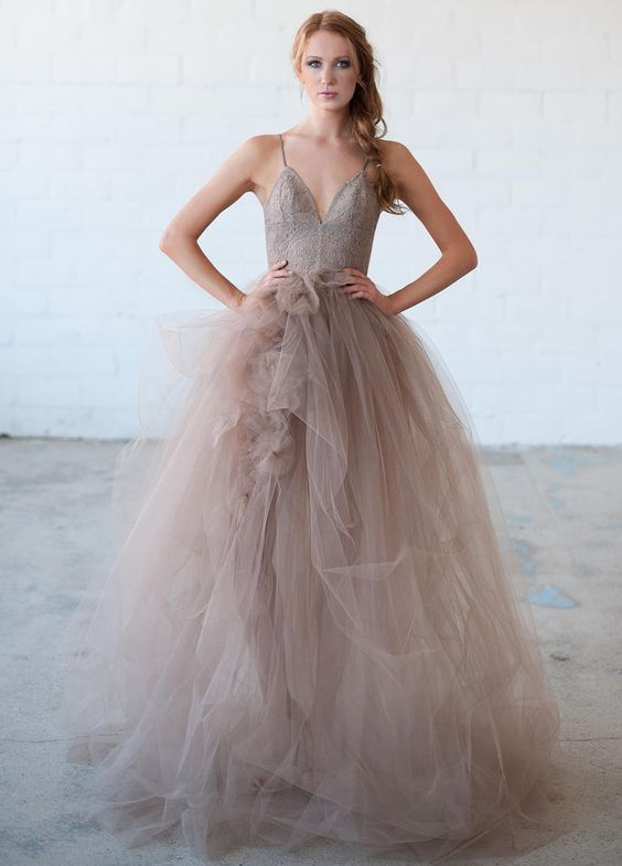 a taupe wedding dress with a layered tulle skirt with fabric blooms and a lace fitting bodice on spaghetti straps