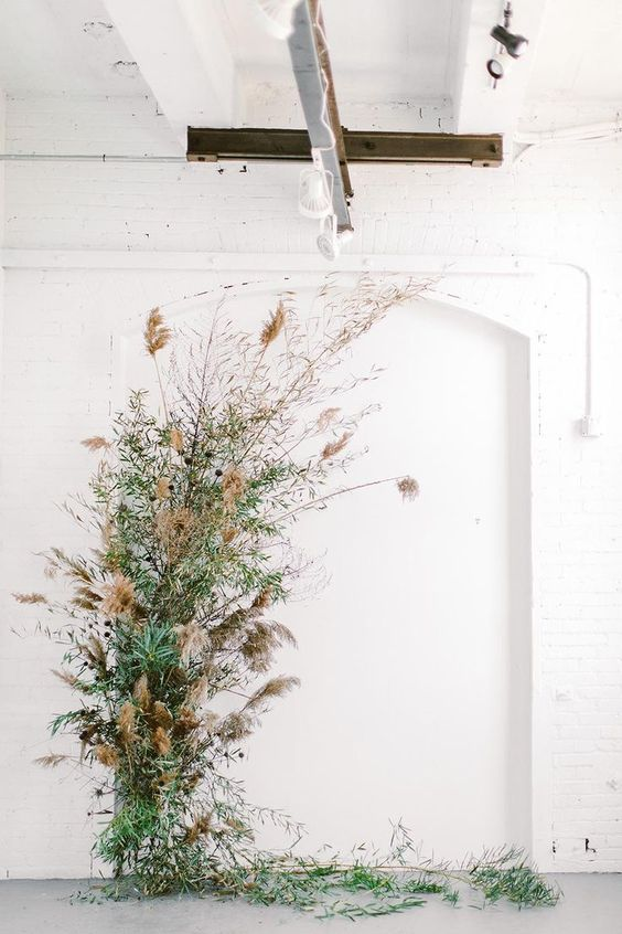 a wedding altar made of greenery and dried grasses is a lovely and chic idea for a modern wedding with a botanical feel