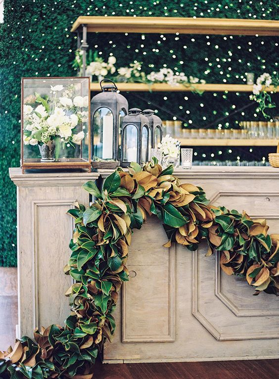 a wedding bar decorated with a lush magnolia leaf garland is a cool idea to spruce up your space
