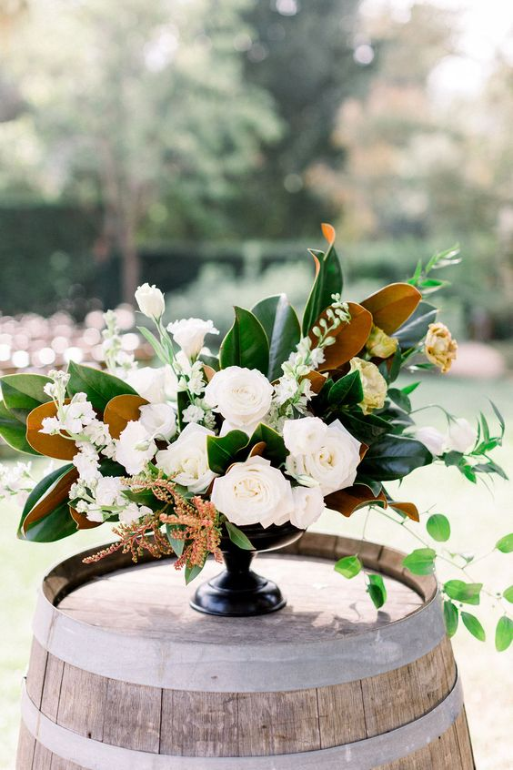 a wedding centerpiece is made of magnolia leaves, white blooms and herbs is a chic and dimensional idea