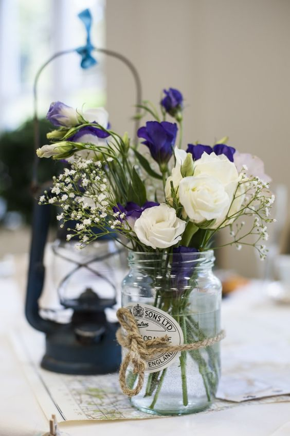 a wedding centerpiece of a jar with twine, with white and bright blue blooms, baby's breath is a lovely idea to try for a rustic wedding