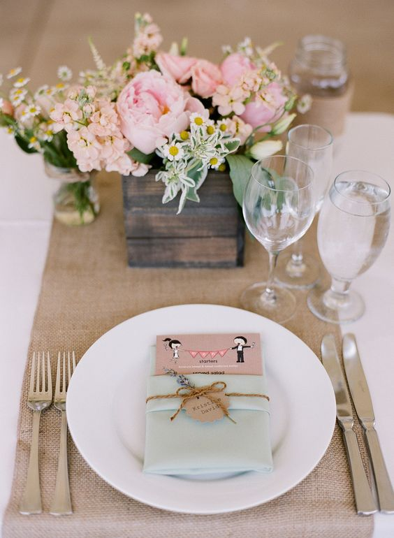 a wedding manu in a mint-colored pocket with twine and a cardboard heart is a lovely idea for a rustic wedding