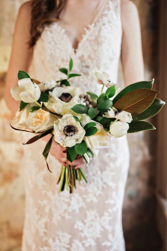 a white anemone wedding bouquet with magnolia leaves and greenery is a chic and non-traditional idea