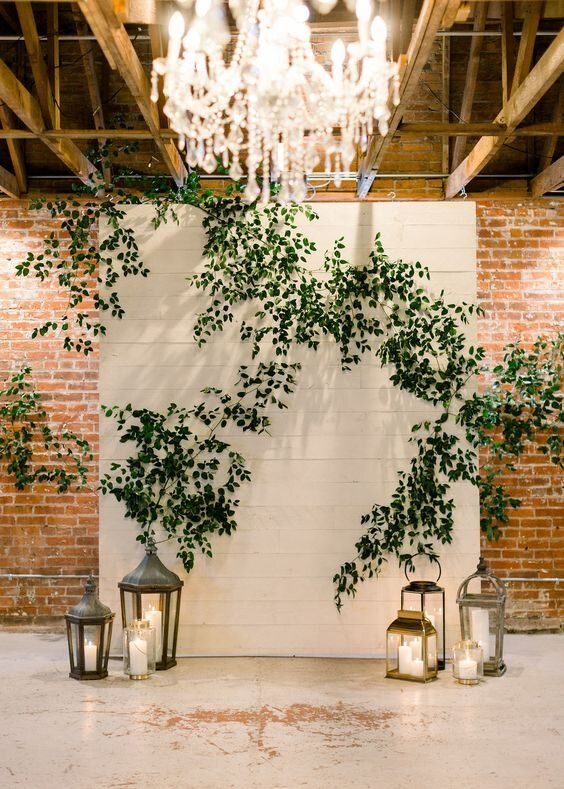 a white backdrop decorated with foliage and with vintage candle lanterns around to form a chic and beautiful wedding ceremony space