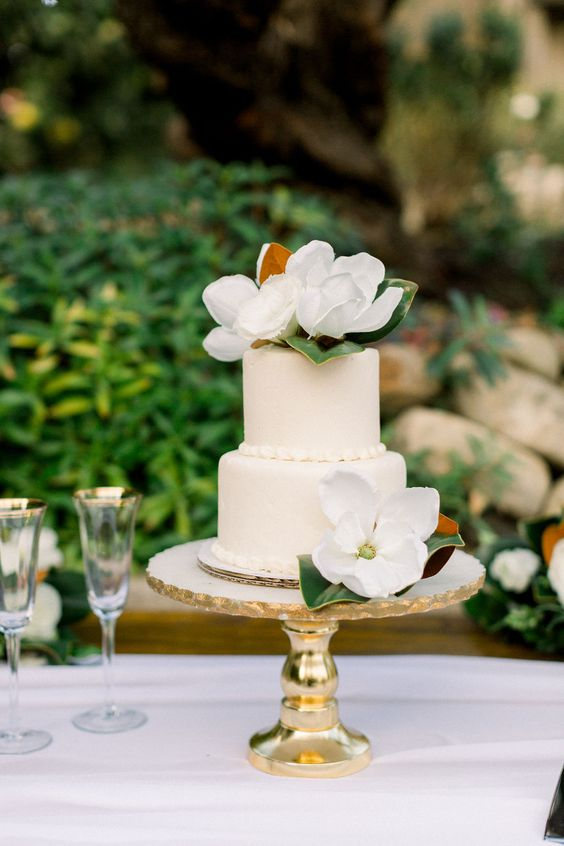 a white wedding cake with magnolia blooms and leaves is a cool and elegant idea on a gold wedding stand