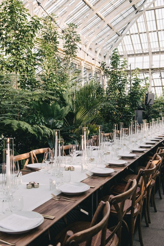 an amazing botanical wedding venue with potted plants and vines around and white linens and candles is wow
