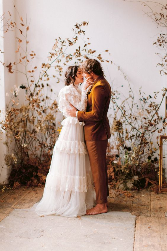 an indoor wedding backdrop of dried leaves, blooms and grasses looks decadent and very stylish, ideal for a fall wedding
