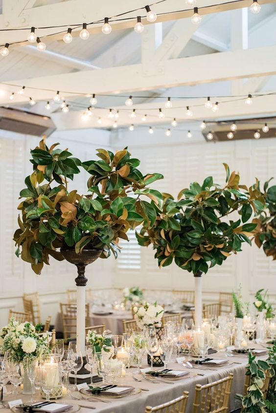 catchy tall wedding centerpieces of magnolia leaves paired with white bloom centerpieces make up a cool wedding decor combo