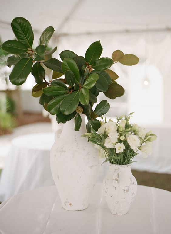 chic and elegant wedding centerpiece of two white vases with magnolia leaves and white blooms