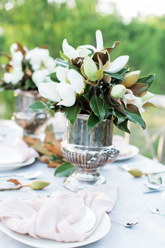 elegant vintage wedding centerpieces of silver urns and lush magnolias - blooms and leaves for chic decor