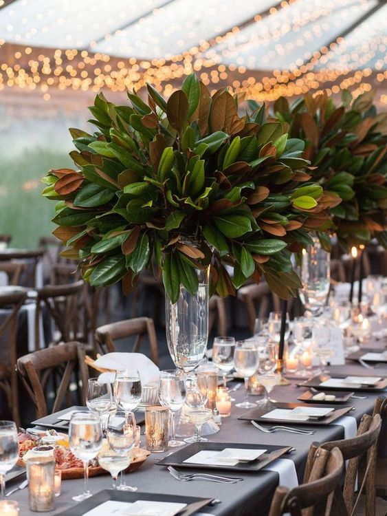 tall wedding centerpieces of clear glass vases and lush magnolia leaves is a cool idea to skip florals