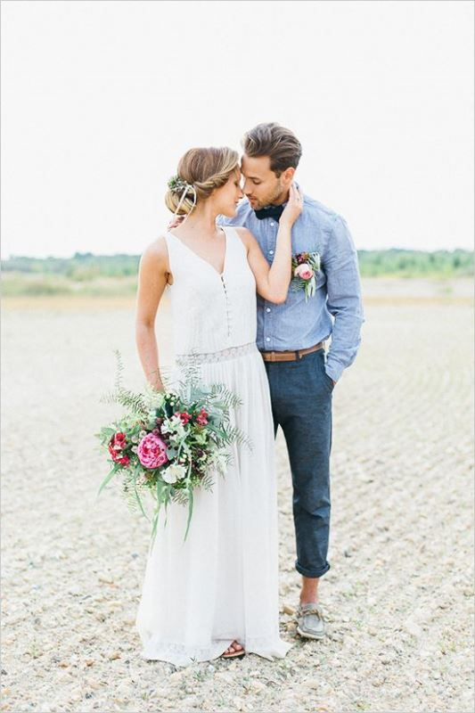 a relaxed groom outfit with navy pants, a chambray shirt, a dark bow tie and loafers with no socks