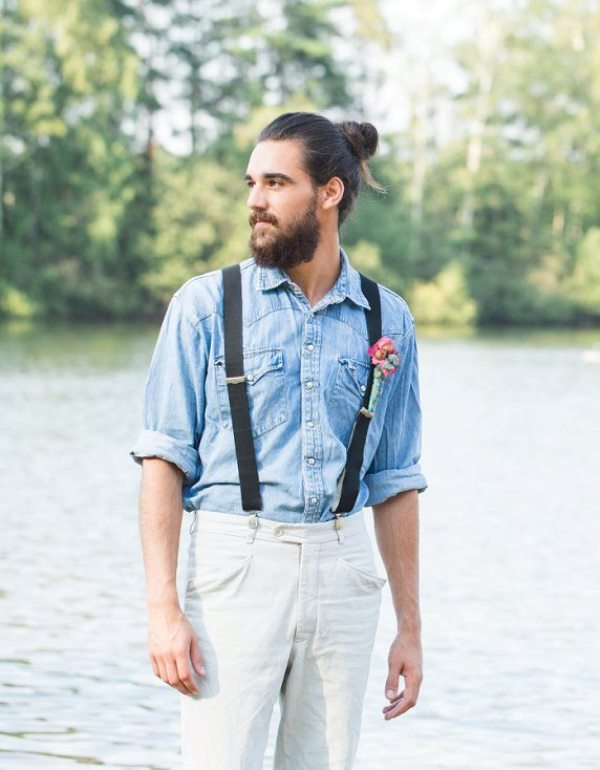 an informal groom's look with white jeans, a blue chambray shirt and suspenders is very relaxed