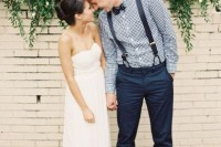 an informal groom's look with navy pants and suspenders, a blue gingham shirt and brown shoes for a rustic touch