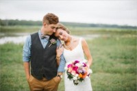 a rustic groom's outfit with mustard pants, a blue shirt, a graphite grey waistcoat and a chain for a vintage touch
