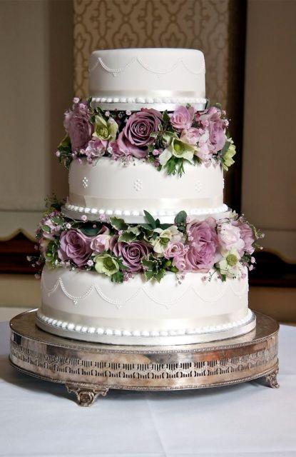 a refined white wedding cake with patterns and lilac and green blooms and greenery between the tiers