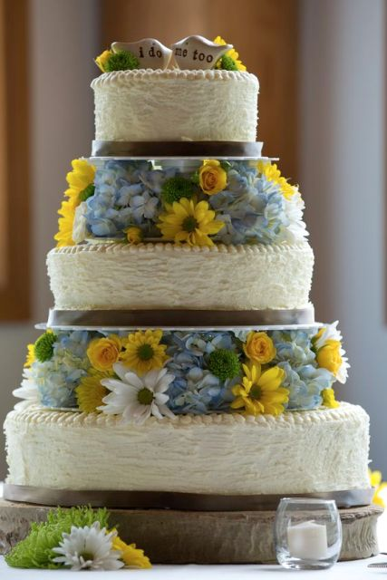 a rustic wedding cake with textural tiers, bright yellow and blue blooms between the tiers and cute bird toppers