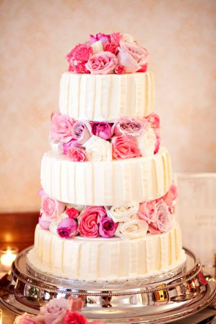 a bold wedding cake with textural white tiers and bright pink blooms between the tiers