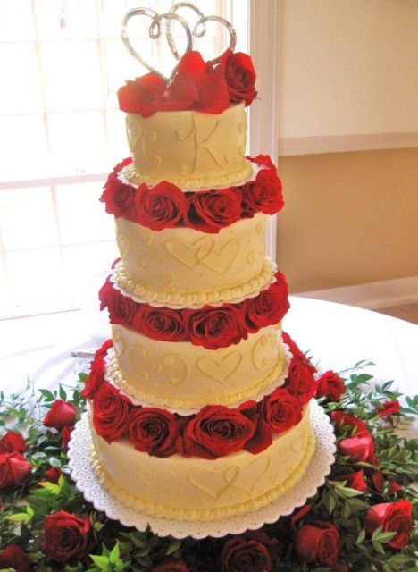 a white patterned wedding cake with bright red blooms between the tiers is super bold and romantic