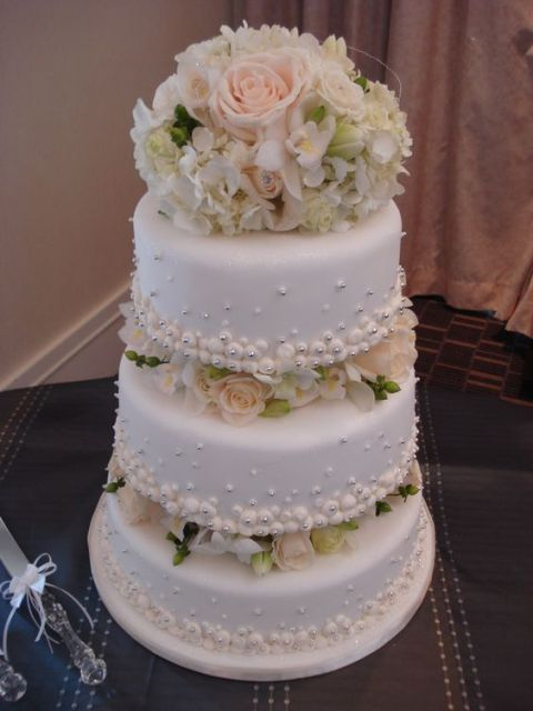 a chic neutral wedding cake with blush and neutral blooms and greenery between the tiers is very elegant