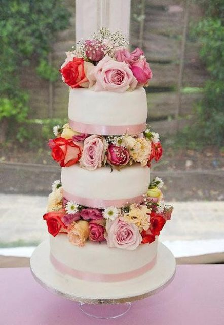 a bright and chic white wedding cake with pink ribbons and colorful flowers between the tiers is very catchy