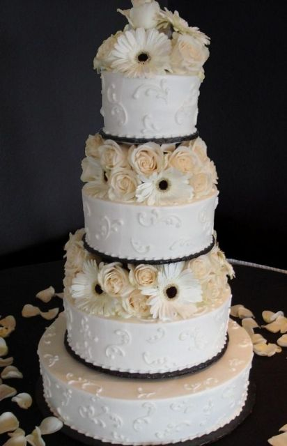 a bright white patterned wedding cake with white and blush blooms between the tiers is very bold