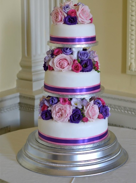 a colorful wedding cake with white tiers and purple and pink blooms between the tiers is wow