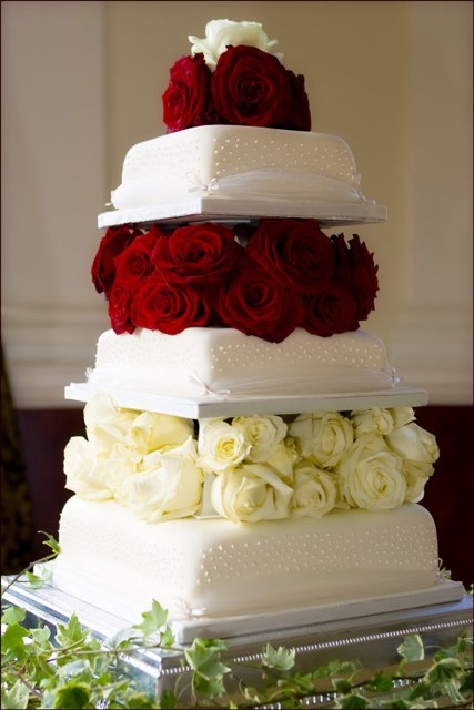 a white blingy wedding cake with white and burgundy roses between the tiers for more elegance