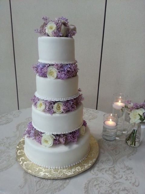 a romantic white wedding cake with purple and white blooms between the tiers is very romantic and tender
