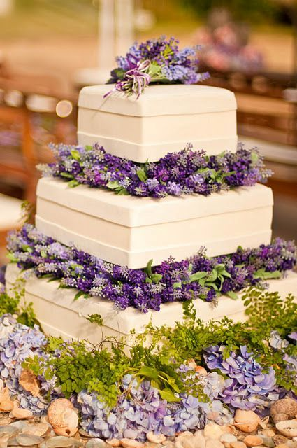 a bold square wedding cake with purple and lilac blooms plus greenery between the tiers