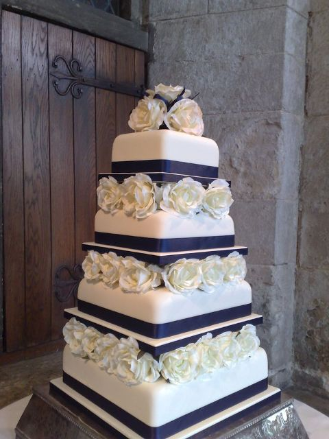 a bold contrasting wedding cake in white and navy and white roses between the tiers for a bold look