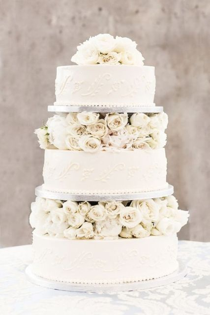 a white patterned wedding cake with white blooms between the tiers is very exquisite and chic