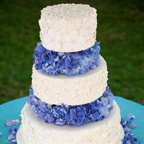 a gorgeous white floral wedding cake with bright blue hydrangeas between the tiers is super catchy and very cool