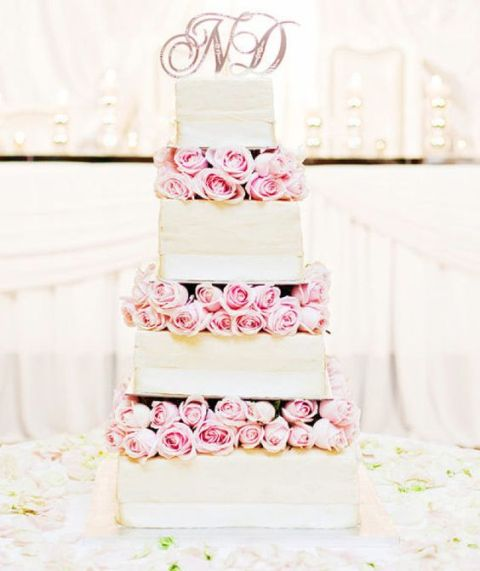 a romantic square wedding cake with pink roses between the tiers and white ribbons is chic and very inspiring