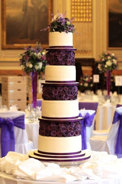 a bold white wedding cake with purple ribbons and deep purple blooms between the tiers