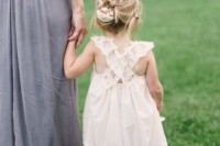 a lace midi dress with a criss cross back and no sleeves, an updo and cowboy boots for a rustic summer wedding