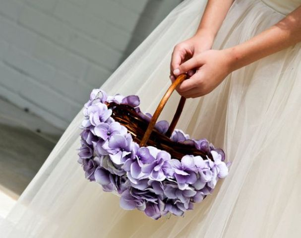 a flower girl basket decorated with purple blooms is a beautiful option