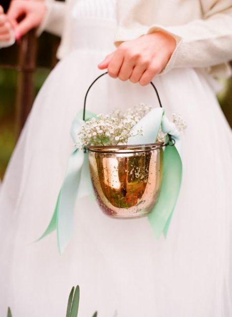 a copper jar used as a basket with green bows and baby's breath is a unique take on a traditional piece