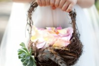 a vine basket decorated with feathers and succulents is a non-traditional idea