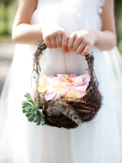 a vine basket decorated with feathers and succulents is a non traditional idea