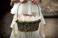 a woven basket decorated with moss, blush ribbon bows and blush petals