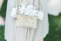 a box with a vine handle, white roses and some greenery and blooms for decor