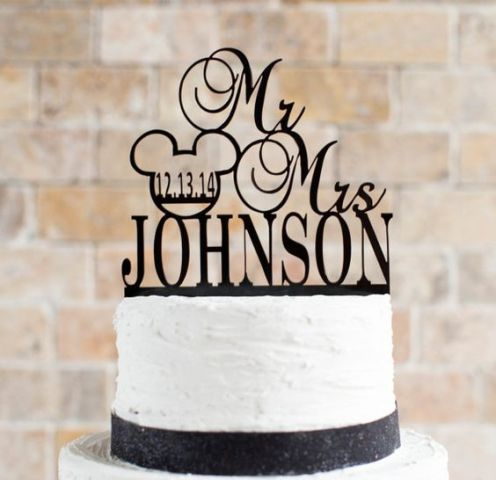a white wedding cake with black ribbon and a topper plus a Mickey Mouse head