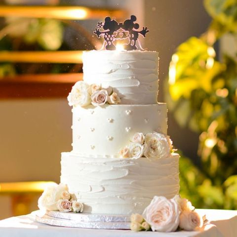 a white textural wedding cake decorated with fresh blooms and a Mickey and Minnie Mouse topper